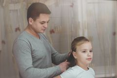 Caring father. Father styling hair of his daughter at home while caring about her.  royalty free stock images
