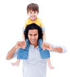 Caring father giving piggyback ride to his boy. Caring father giving piggyback ride to his little boy isolated on a white background Stock Photo