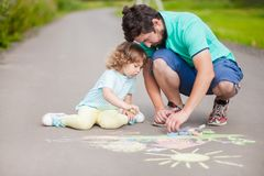 Cute toddler girl and her father drawing with color chalk. Caring father, happy family. Drawing with color chalk. Happy childhood. Preschooler leisure time Stock Photo