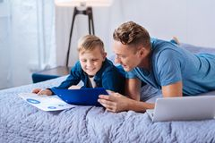 Caring father helping son with his school project. Let me help. Pleasant loving father lying on the bed next to his little son and studying with him printouts Royalty Free Stock Image