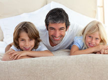 Caring father and his children lying on a bed. At home Stock Images