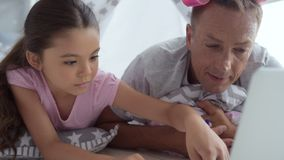 Caring father and his little daughter using laptop at home stock video