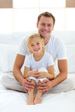 Caring father with his little girl sitting on bed royalty free stock photo