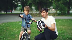 Caring father is holding bicycle helmet and talking to his adorable son explaining safety regulations while boy is. Caring father is holding protective bicycle stock video footage