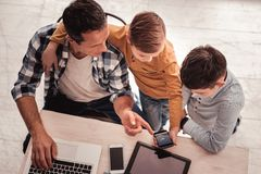 Caring father joining his cute sons while watching photos stock photos
