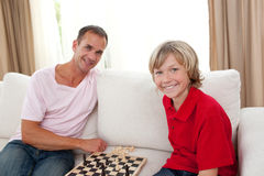 Caring father playing chess with his son. At home stock image