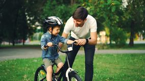 Caring father is putting safety helmet on his little son`s head then teaching happy boy to ride bicycle while loving. Caring father is putting safety helmet on stock footage