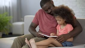 Caring father reading fairy tales aloud to his little daughter, family love