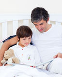 Caring father reading with his son. Sitting on a bed Royalty Free Stock Photos