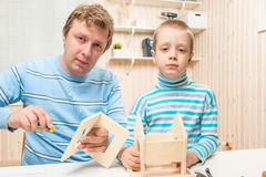 Caring father teaches his son to build bird feeder Royalty Free Stock Photography