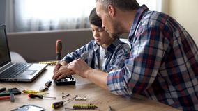 Caring father teaching his little son to repair hard disk drive at home, hobby royalty free stock photography