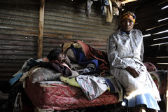 A caring friend. A woman sitting next to her sick friend in a rural area in Natal in South Africa. The lady in bed has TB and is HIV positive, she is very sick Royalty Free Stock Images
