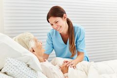 Nursing lady looks after a sick elderly woman. Caring geriatric nurse cares for ill senior citizen in nursing home or hospice stock photos