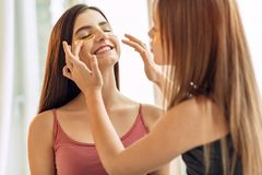 Caring girl adjusting under-eye patches on sisters face Stock Photography