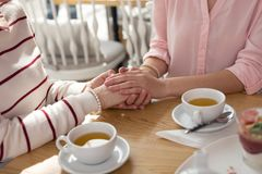 Caring girl holding hands with her granny. Best granny. Loving caring granddaughter holding hands with her granny while having tea Royalty Free Stock Photography