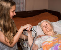 Caring girl holding old lady's hands stock images