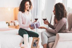 Caring girl presenting wonderful gift to her best friend. Wonderful gift. Caring beautiful girl presenting wonderful unexpected gift to her charming best friend stock photos