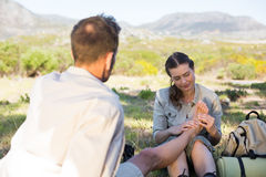 Caring girlfriend giving her boyfriend a foot rub on a hike Stock Photo