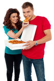 Caring girlfriend making her boyfriend eat pizza Stock Photo
