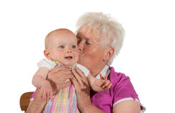 Caring granny kissing her grandchild. Caring granny kissing her little grandchild - isolated on white Stock Photos