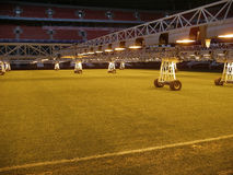 Caring for grass lawn. Lighting installation on soccer stadium Royalty Free Stock Photos