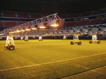 Caring for grass lawn. Lighting installation on soccer stadium Stock Images