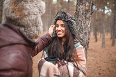 The guy corrects the hat on the girl`s head, the girl smiles . Outdoors in forest. Stock Images