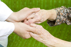 Caring hand. A male doctor holding an elderly woman's hand Stock Image
