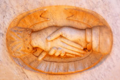 Caring hands. Two caring shaking hands on an ancient marble stone tombstone Royalty Free Stock Images