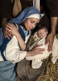 Caring hands at Christmas nativity. Live Christmas nativity scene in an old barn - Reenactment play with authentic costumes. The baby is a (property released) stock photos