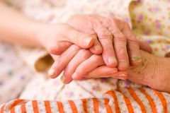 Caring hands - helping the needy. A young hand holding an elderly one. It can be a hand of a carer or a family member Royalty Free Stock Image
