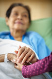 Caring hands. Holding kind elderly lady's hands in bed at hospital Stock Photography