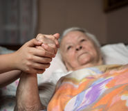 Caring hands holding old lady's hands. In bed at home Stock Photography