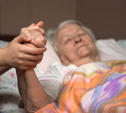 Caring hands holding old lady's hands. In bed at home Stock Photo