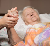 Caring hands holding old lady's hands. In bed at home Royalty Free Stock Photo