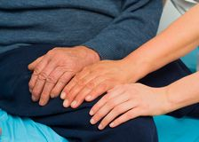 Caring Hands. Supporting hands for elderly disabled man wth several diseases Royalty Free Stock Image