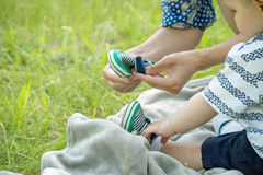 Caring hands of a young mother dressing a child in a summer park on the grass. Caring hands of a young mother dressing a kid in a summer park on green grass Royalty Free Stock Image