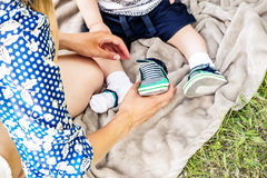 Caring hands of a young mum dressing a little kid in nature in a summer park on the grass. Caring hands of a young mother dressing a kid in a summer park on Royalty Free Stock Photography