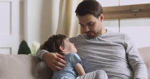 Caring dad embracing preschool son having trust conversation on sofa