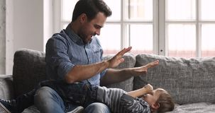 Caring young dad tickling child son laughing playing on sofa