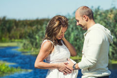 Caring husband with his pregnant wife. Caring husband while touching his pregnant wife's belly Royalty Free Stock Photo
