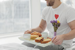 Caring husband holding tray with food in morning Royalty Free Stock Photos