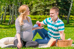 Caring husband offers to his pregnant woman apple Stock Image