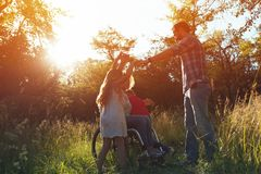 Woman in an armchair has fun with her husband and two children in park royalty free stock photo