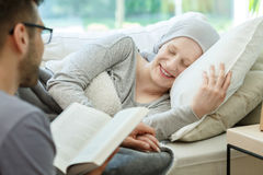 Reading book to cancer survivor. Caring husband reading book to his happy cancer survivor wife Royalty Free Stock Photo