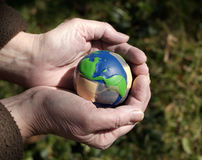 Caring for an injured earth. Hands holding injured bandaged earth Stock Image