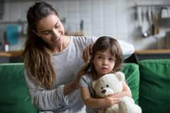 Caring loving mother brushing kid daughters hair sitting on sofa stock photography