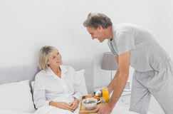 Caring man bringing breakfast in bed to his partner Royalty Free Stock Photo