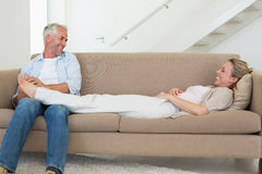 Caring man giving his partner a foot rub on the couch Royalty Free Stock Photos
