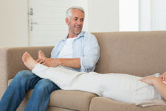 Caring man giving his partner a foot rub on the couch Stock Photo